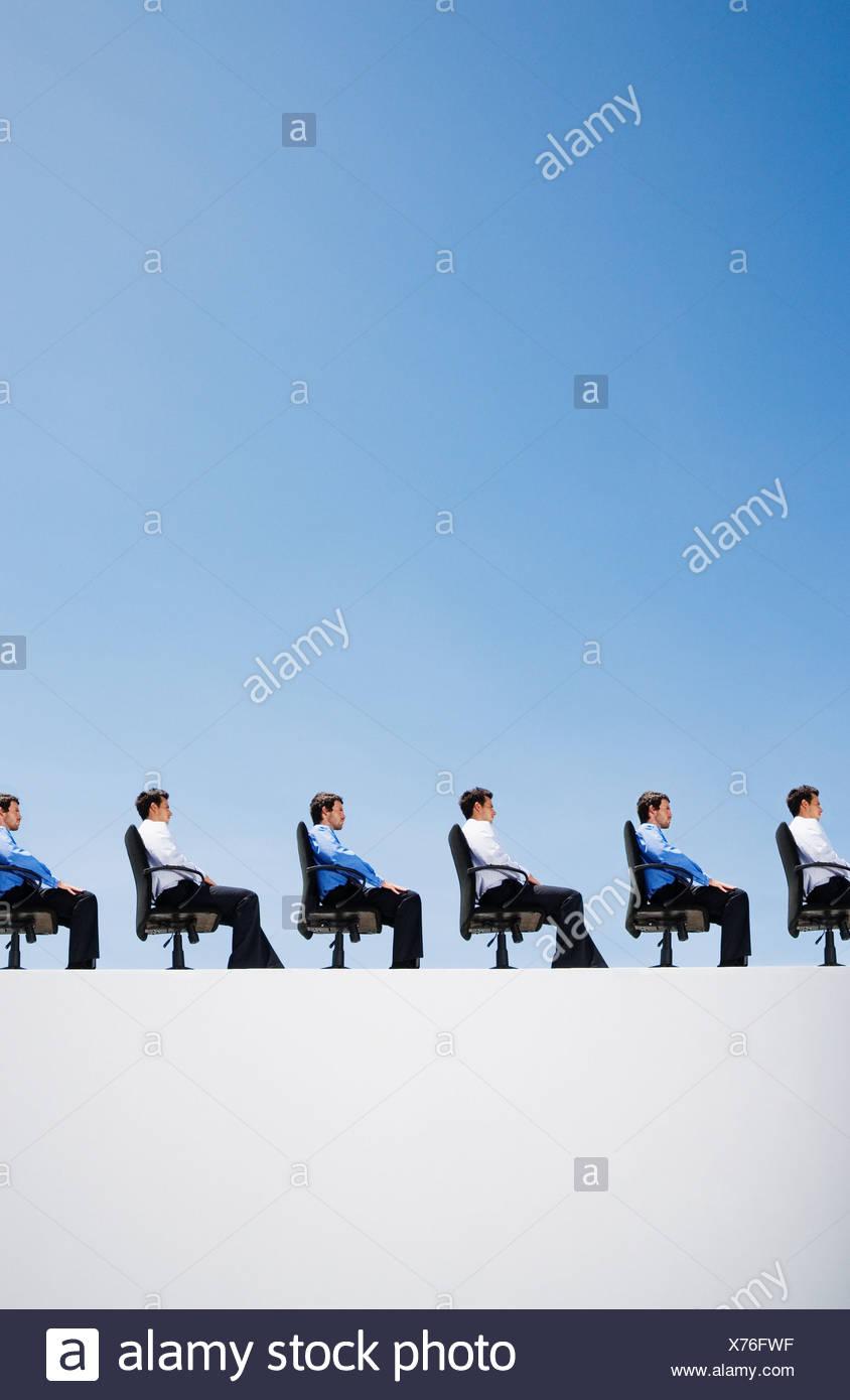 Line-up di imprenditori nel loro sedie per ufficio Immagini Stock