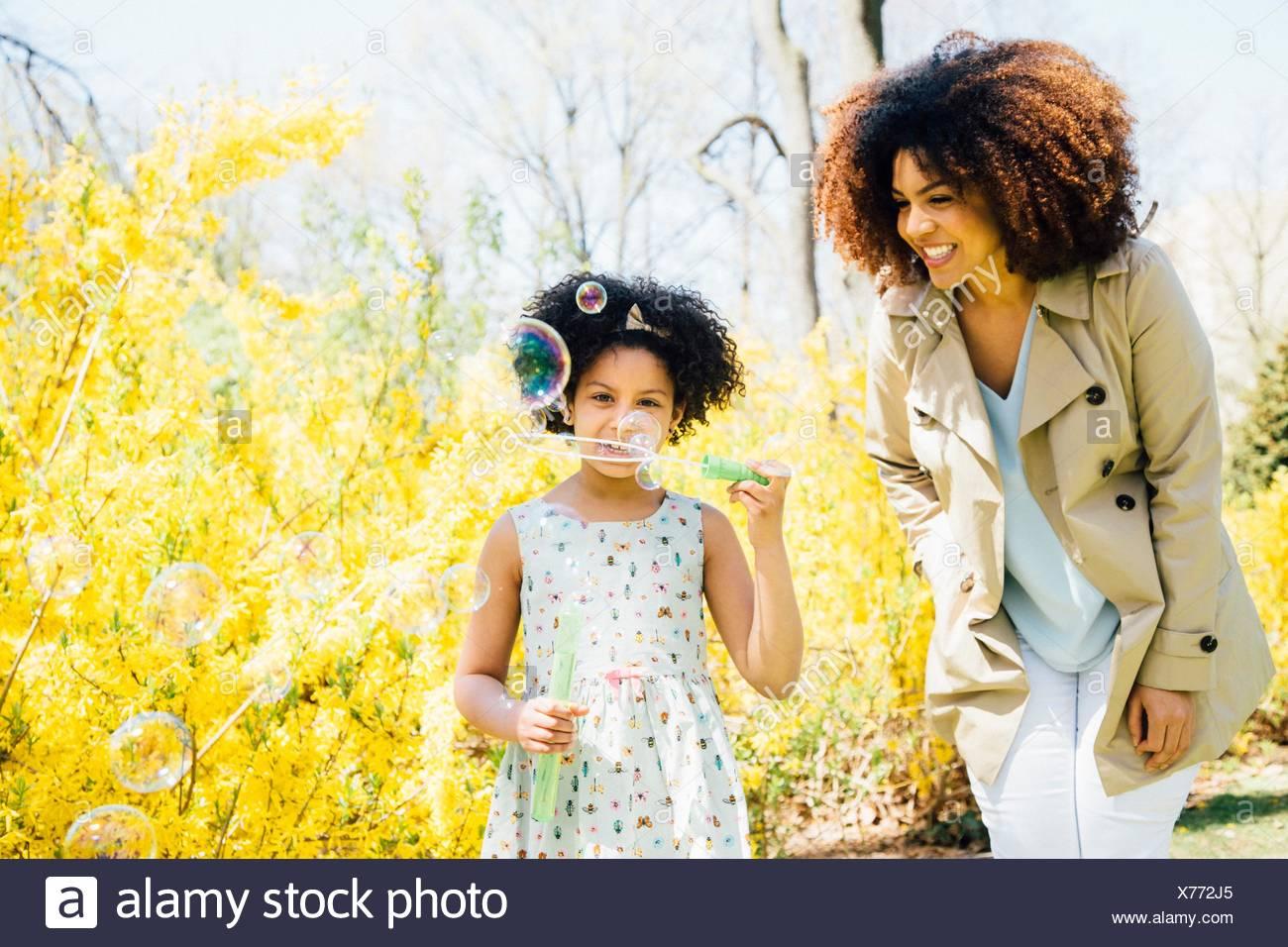 Vista frontale della madre e figlia a soffiare bolle Immagini Stock