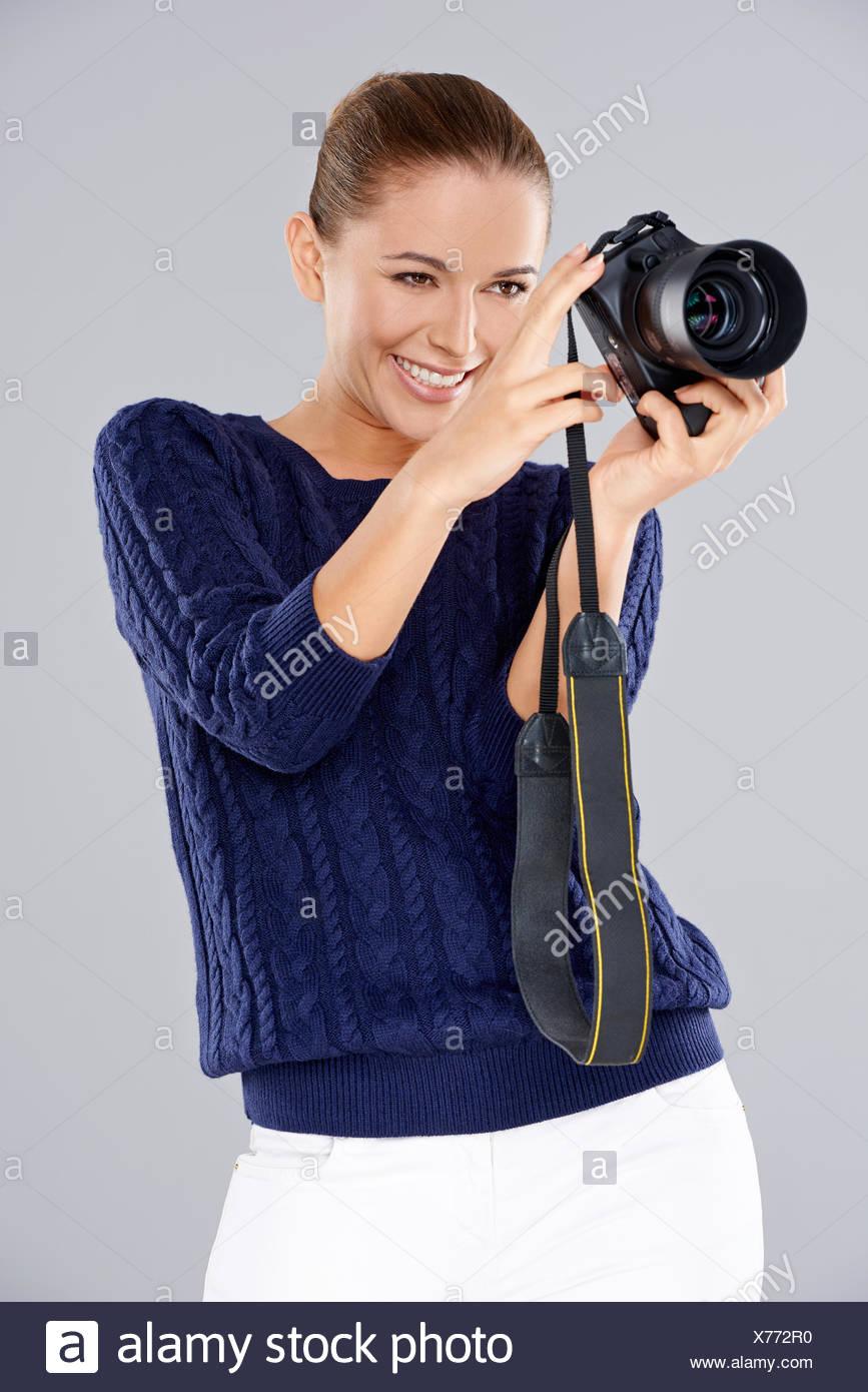 Donna felice tiene una telecamera professionale Immagini Stock