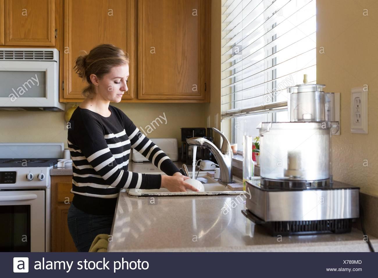 Donna lavaggio fino in cucina Immagini Stock