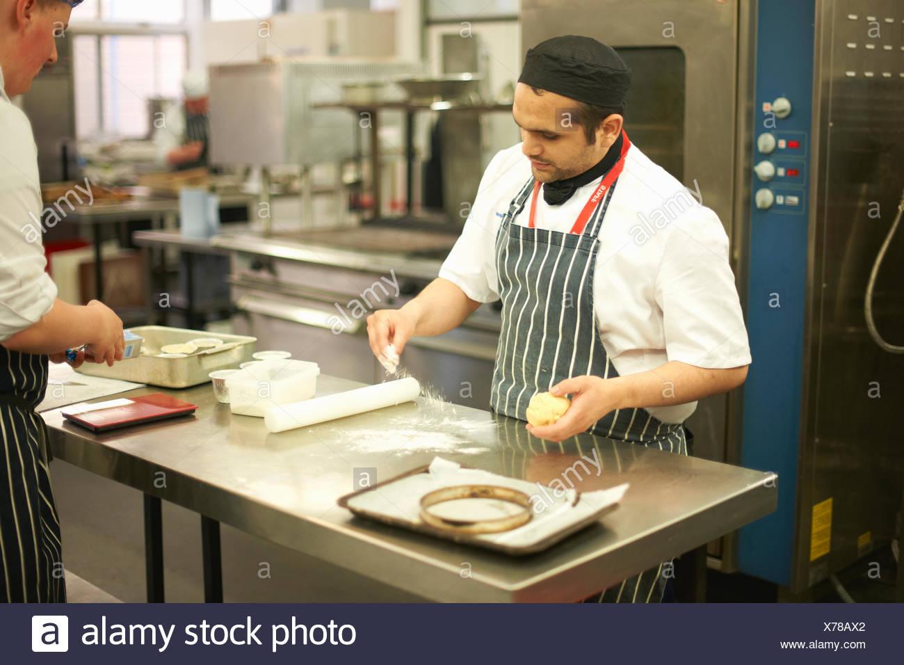 Lo Chef docente dimostrazione tecnica per catering teenage studente al banco di cucina Immagini Stock