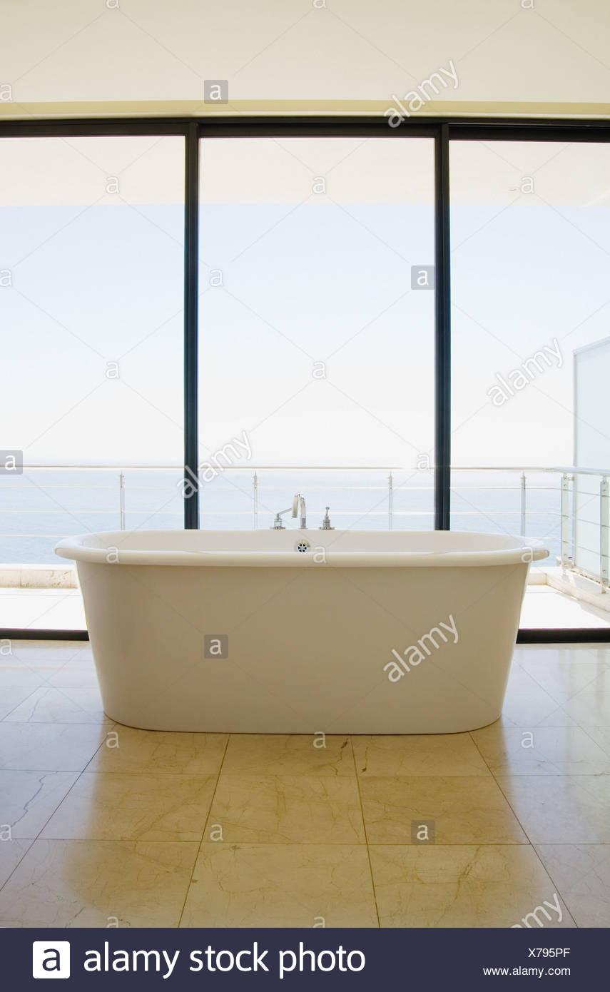 Bagno moderno con vasca da bagno e finestre di grandi dimensioni Immagini Stock