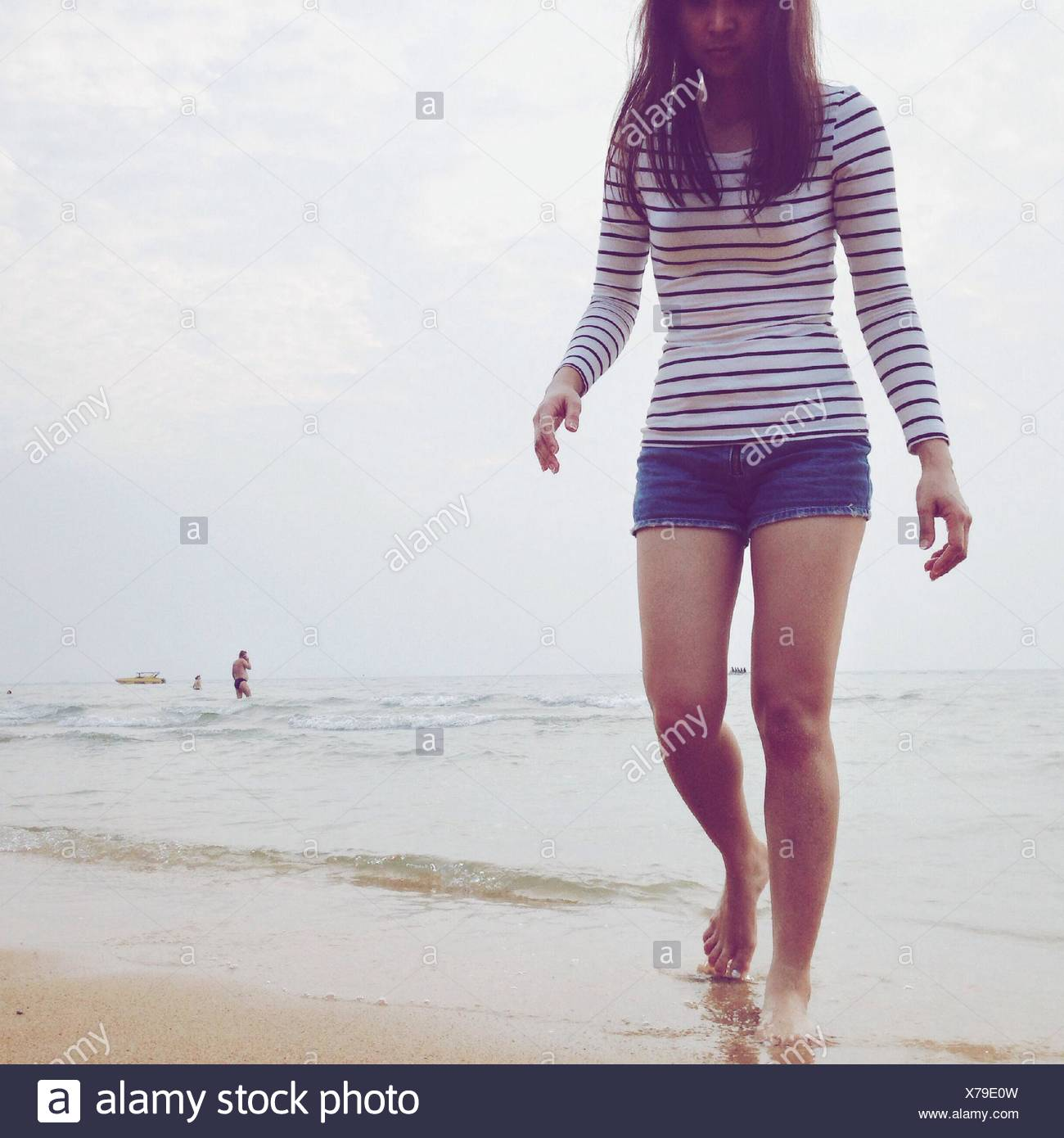 Giovane donna camminando sulla spiaggia Immagini Stock