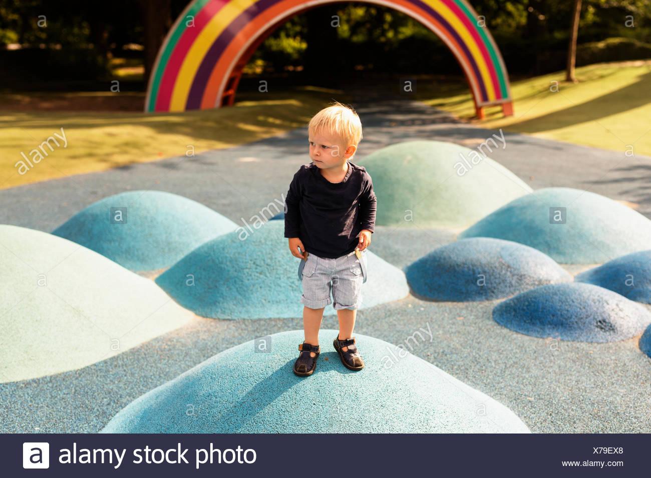 Per tutta la lunghezza del ragazzo in piedi sulla collina artificiale nel parco giochi Immagini Stock