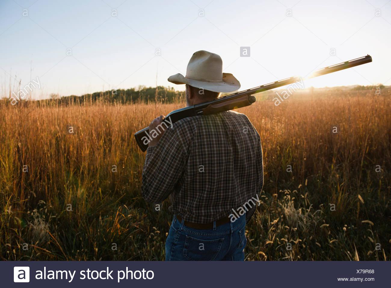 Maschio anziano contadino con un fucile sulla spalla in campo remoto al crepuscolo, Plattsburg, Missouri, Stati Uniti d'America Immagini Stock