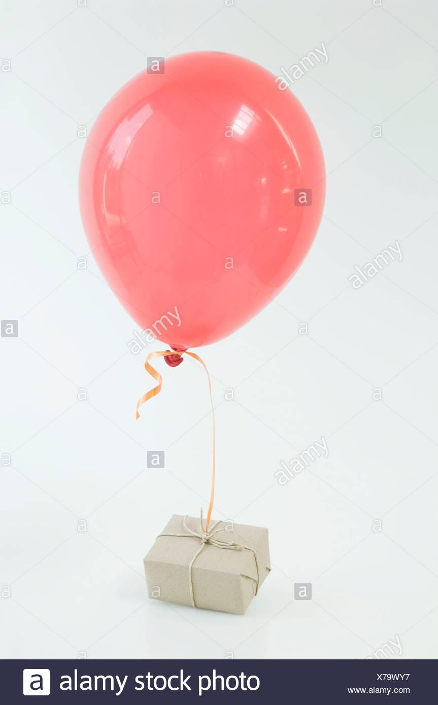 Il palloncino rosso legato alla posta aerea pacco contro uno sfondo bianco, close up Foto Stock