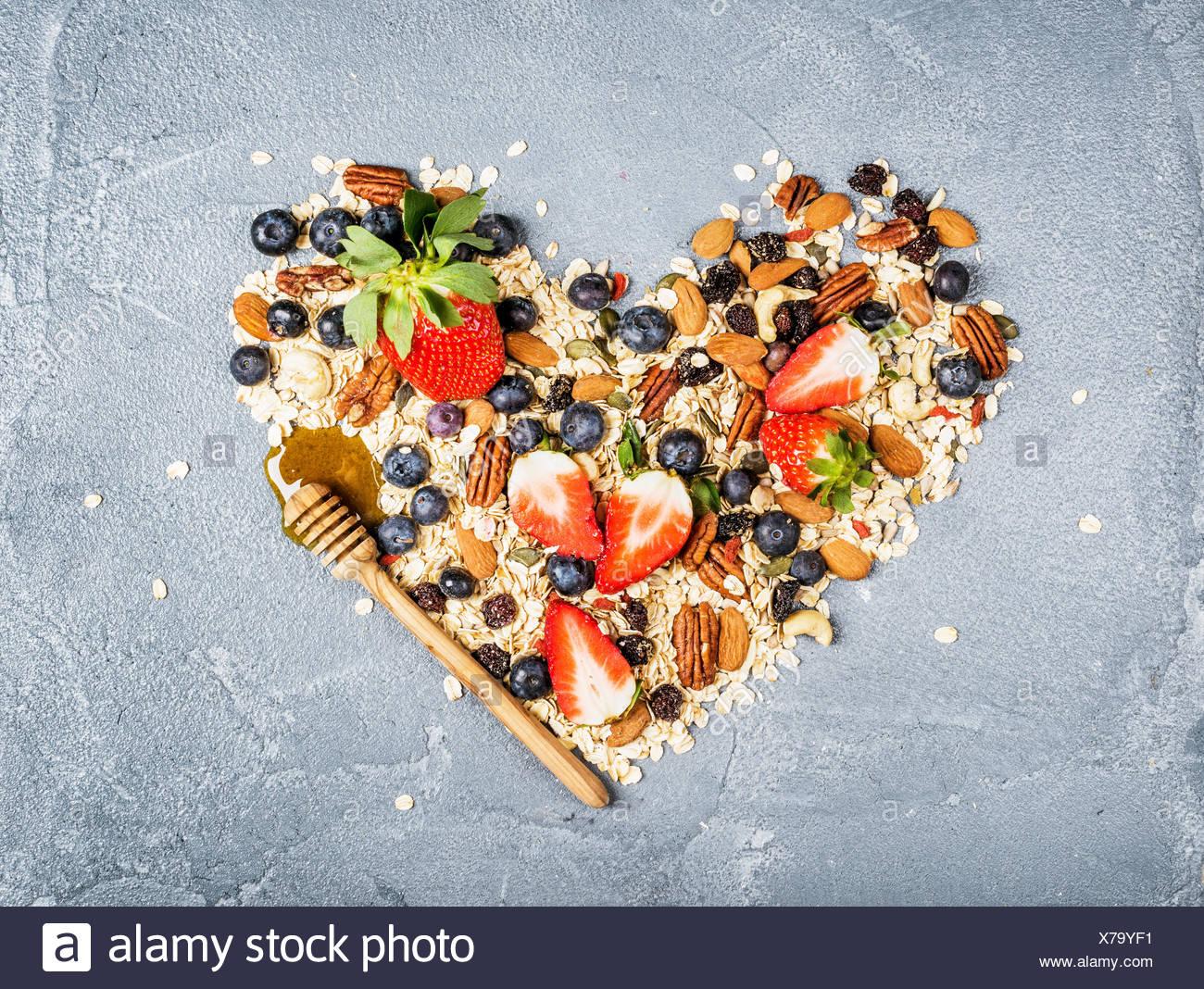 Ingredienti per la cottura sana colazione muesli in forma di cuore. Le fragole mirtilli dadi fiocchi di avena e la frutta secca Immagini Stock