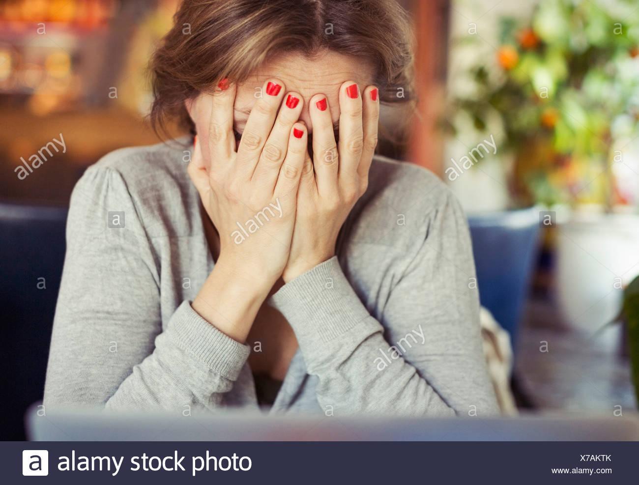 Triste giovane donna seduta con testa in mani a casa Immagini Stock