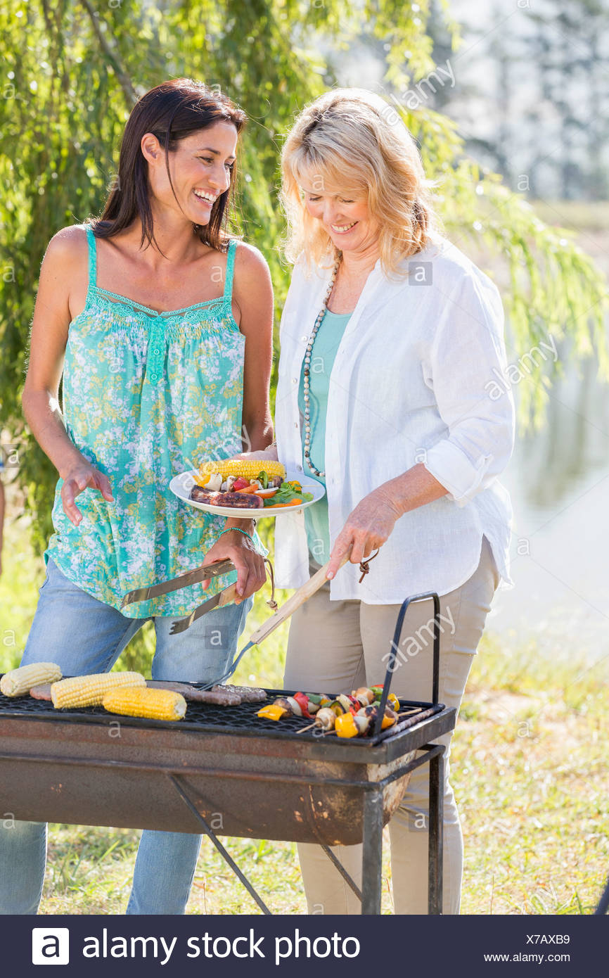 Due donne per la cottura Barbeque In campagna Immagini Stock
