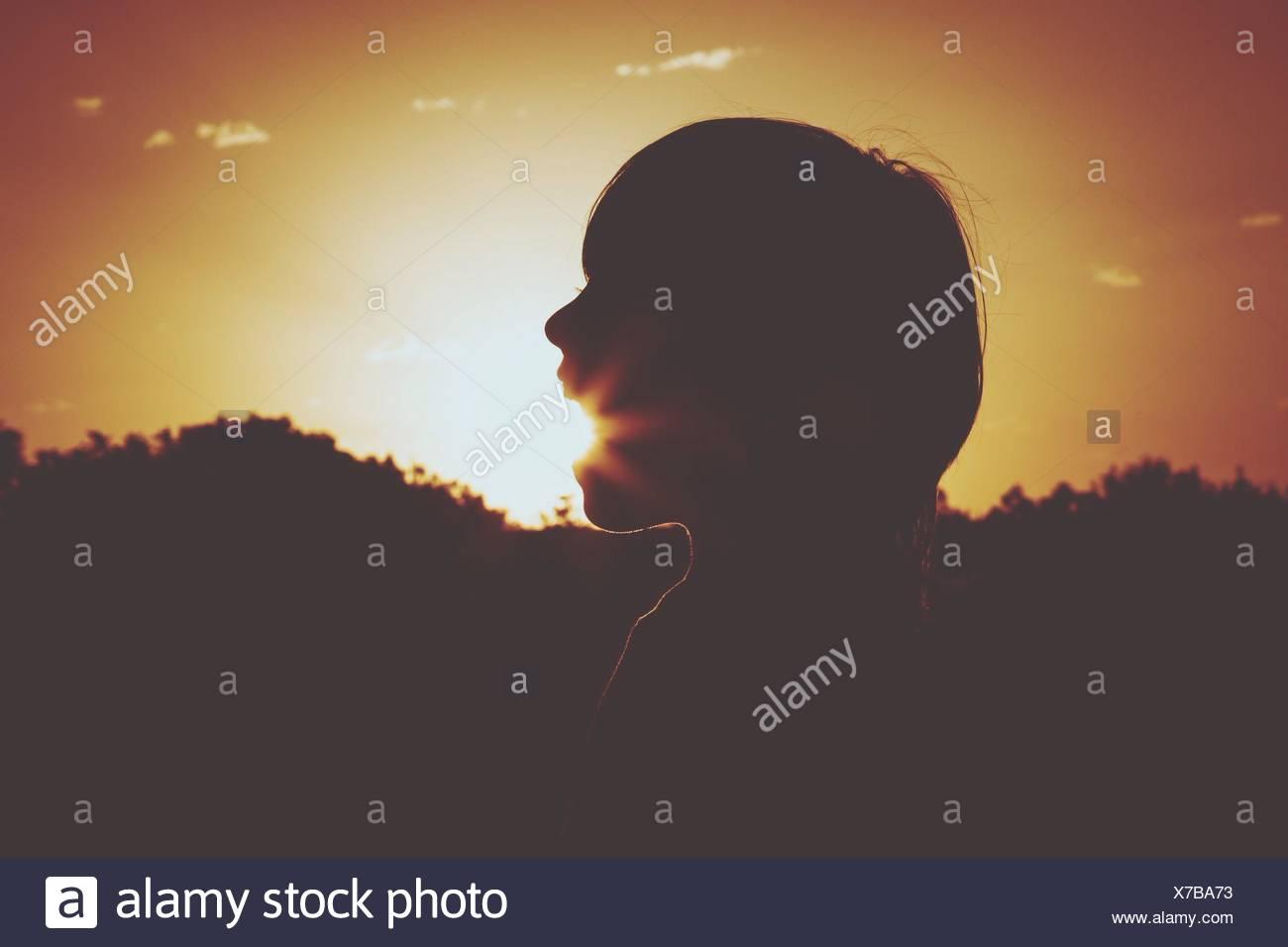 Illusione ottica di Silhouette Boy mangiare sole al tramonto Immagini Stock