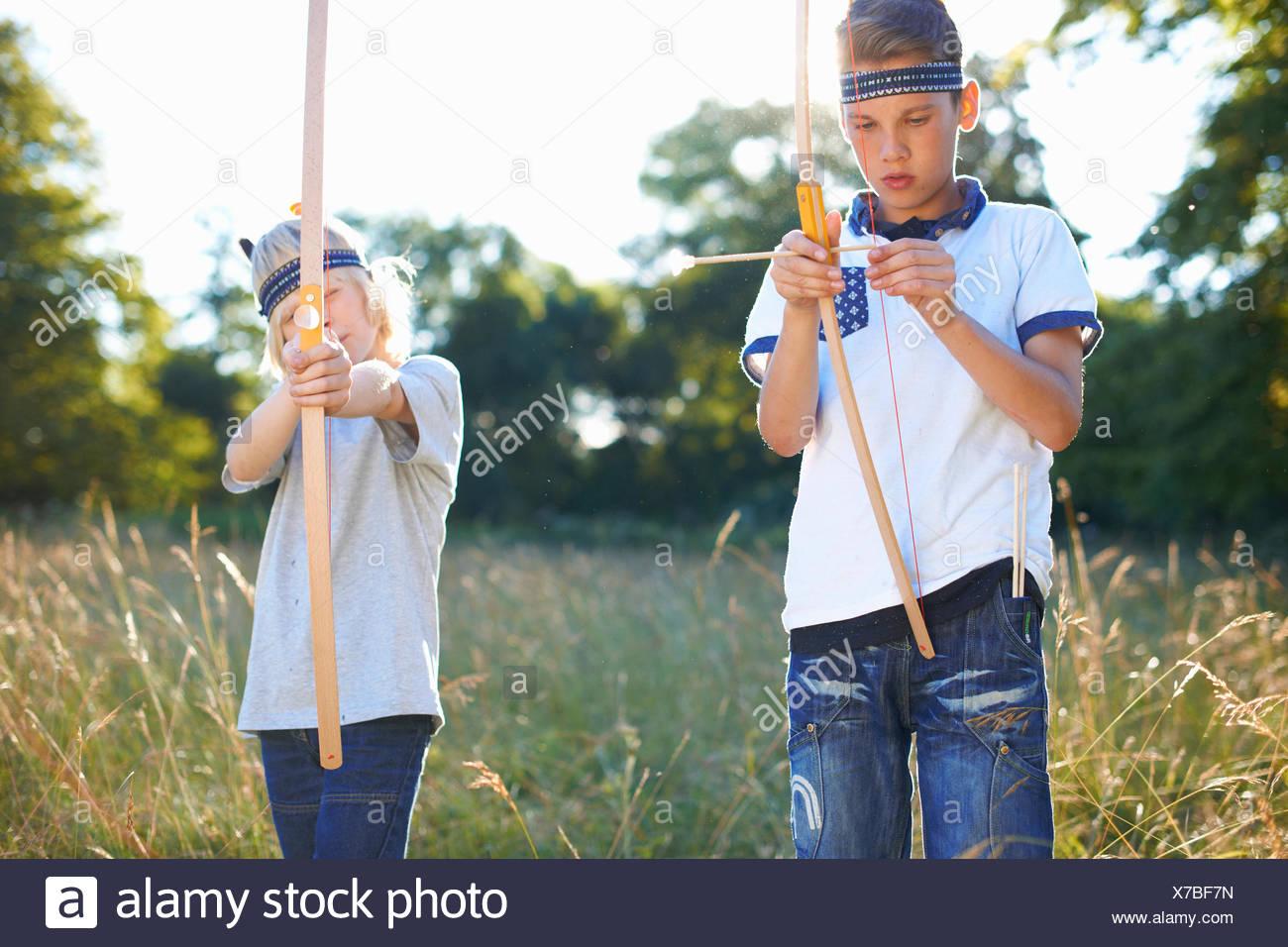 Due giovani ragazzi azienda arco e frecce Immagini Stock