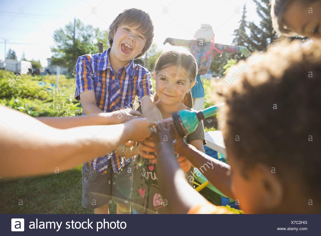 I bambini lavarsi le mani insieme con tubo flessibile da giardino Immagini Stock