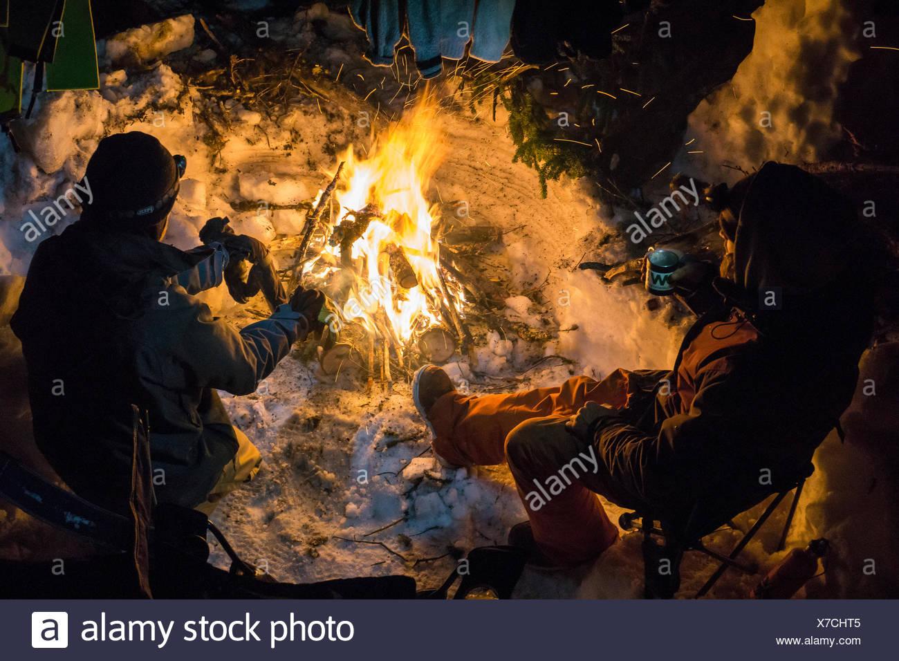 Lo snowboard in fase di riscaldamento bere il tè intorno al fuoco di notte Immagini Stock