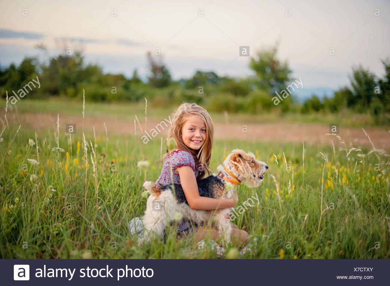 Ritratto di un sorridente ragazza seduta nella campagna che abbraccia il suo fox terrier cane Immagini Stock