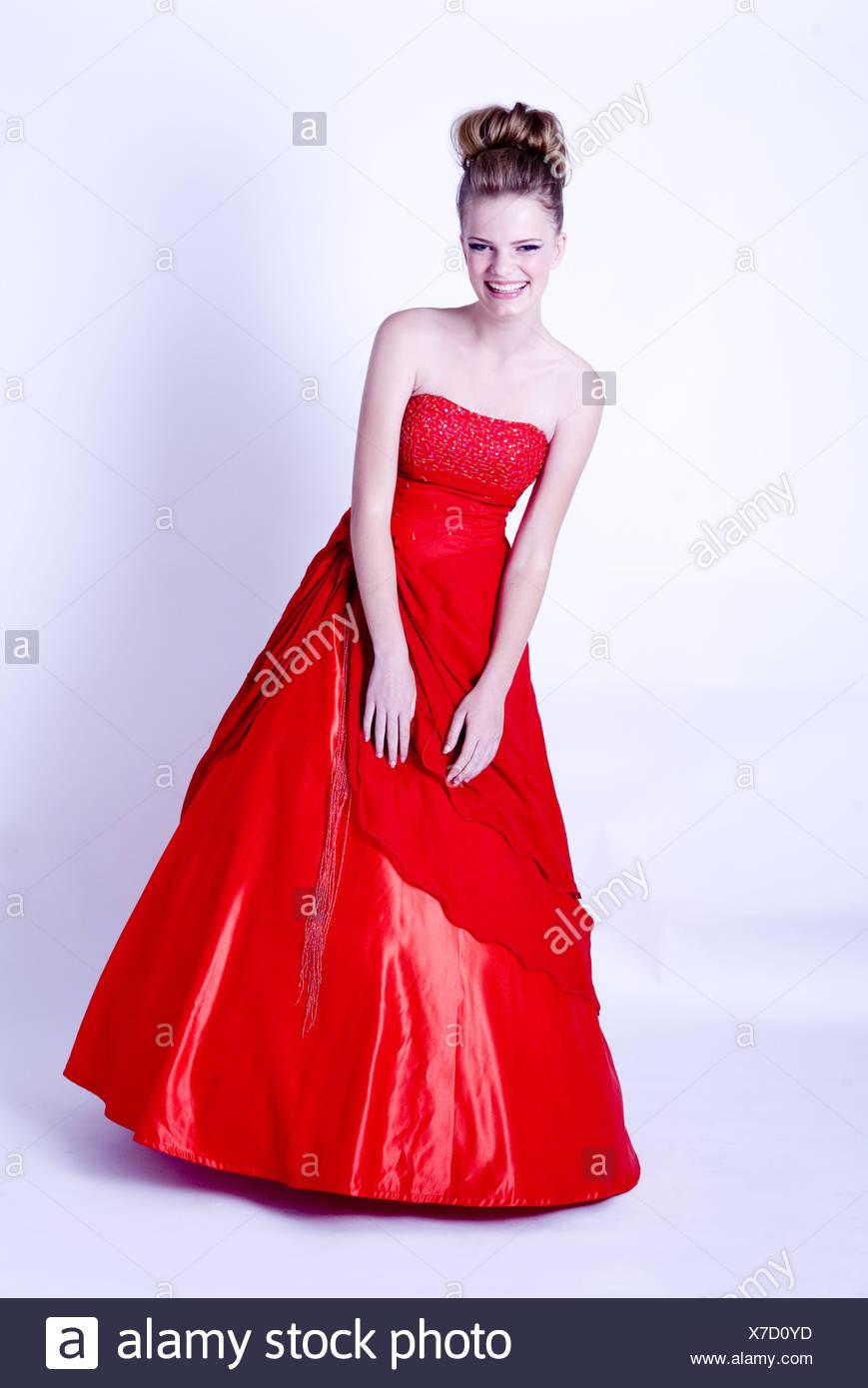 5be7e9c95e4b Ritratto di giovane donna guardare al sorriso della fotocamera e in rosso  Palla abito