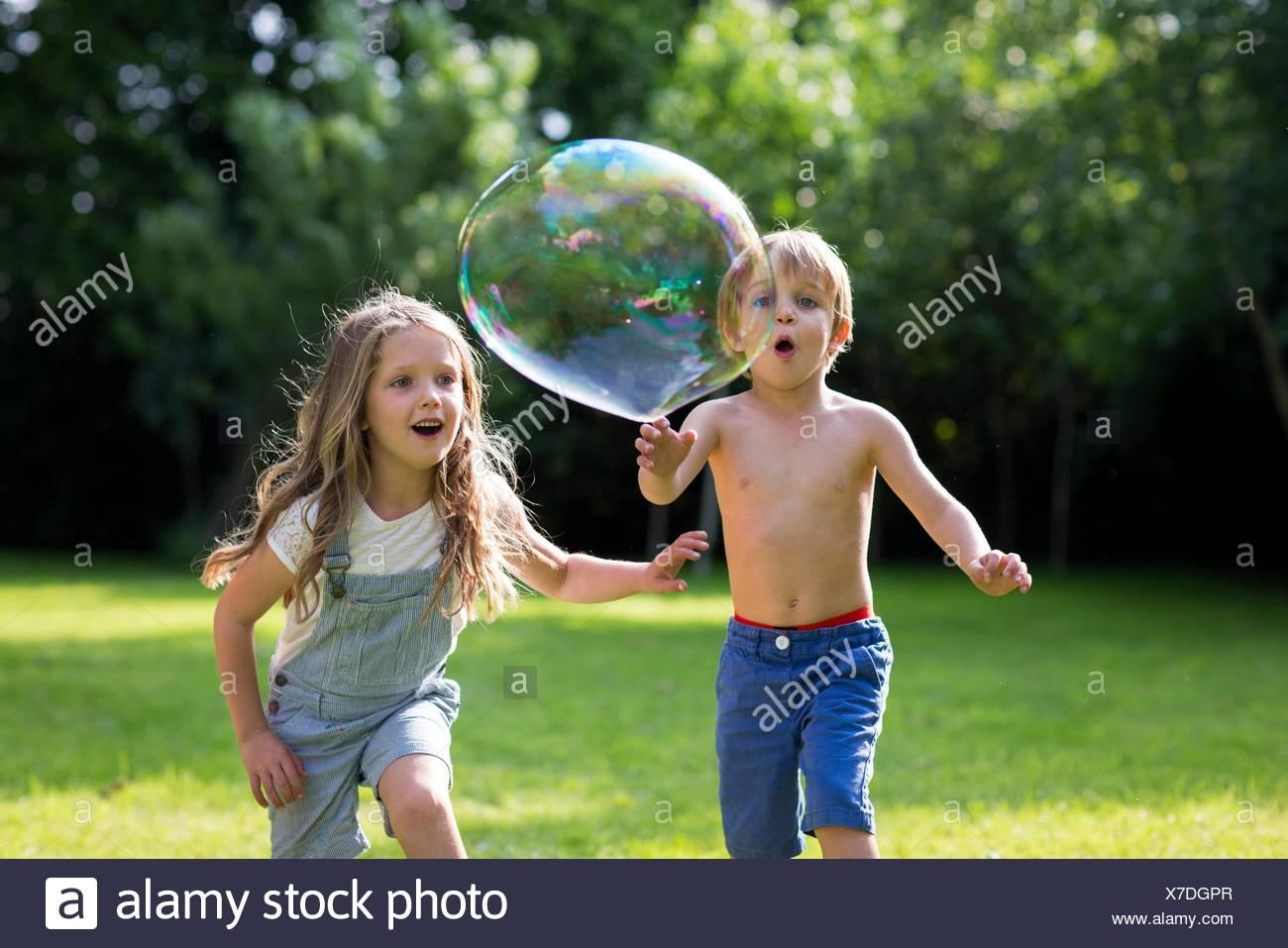 Proprietà rilasciato. Modello rilasciato. Fratello e Sorella a caccia di bolle nel giardino. Immagini Stock