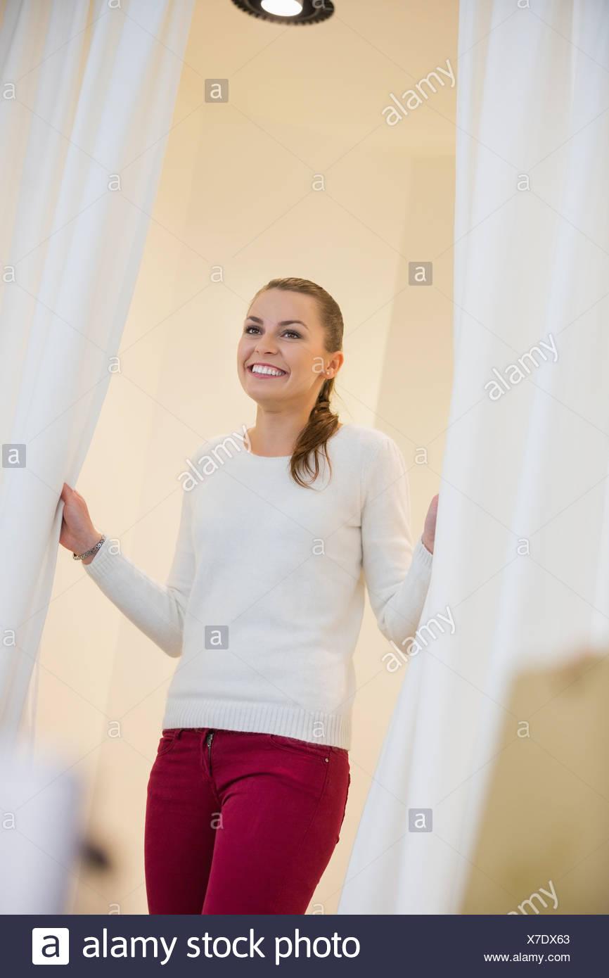 Donna felice in spogliatoio tende di apertura Immagini Stock