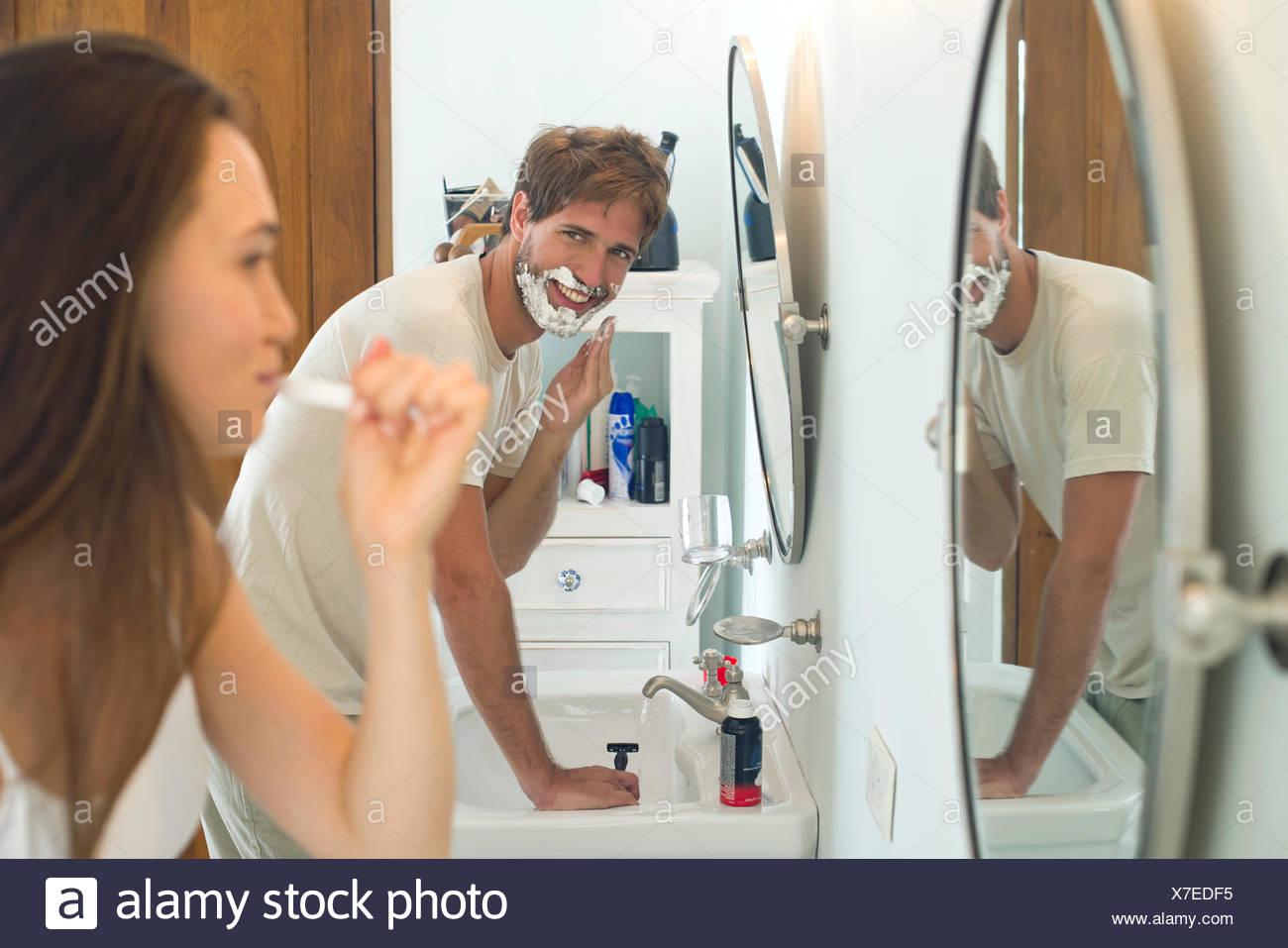 La donna la spazzolatura dei denti, marito la rasatura Immagini Stock