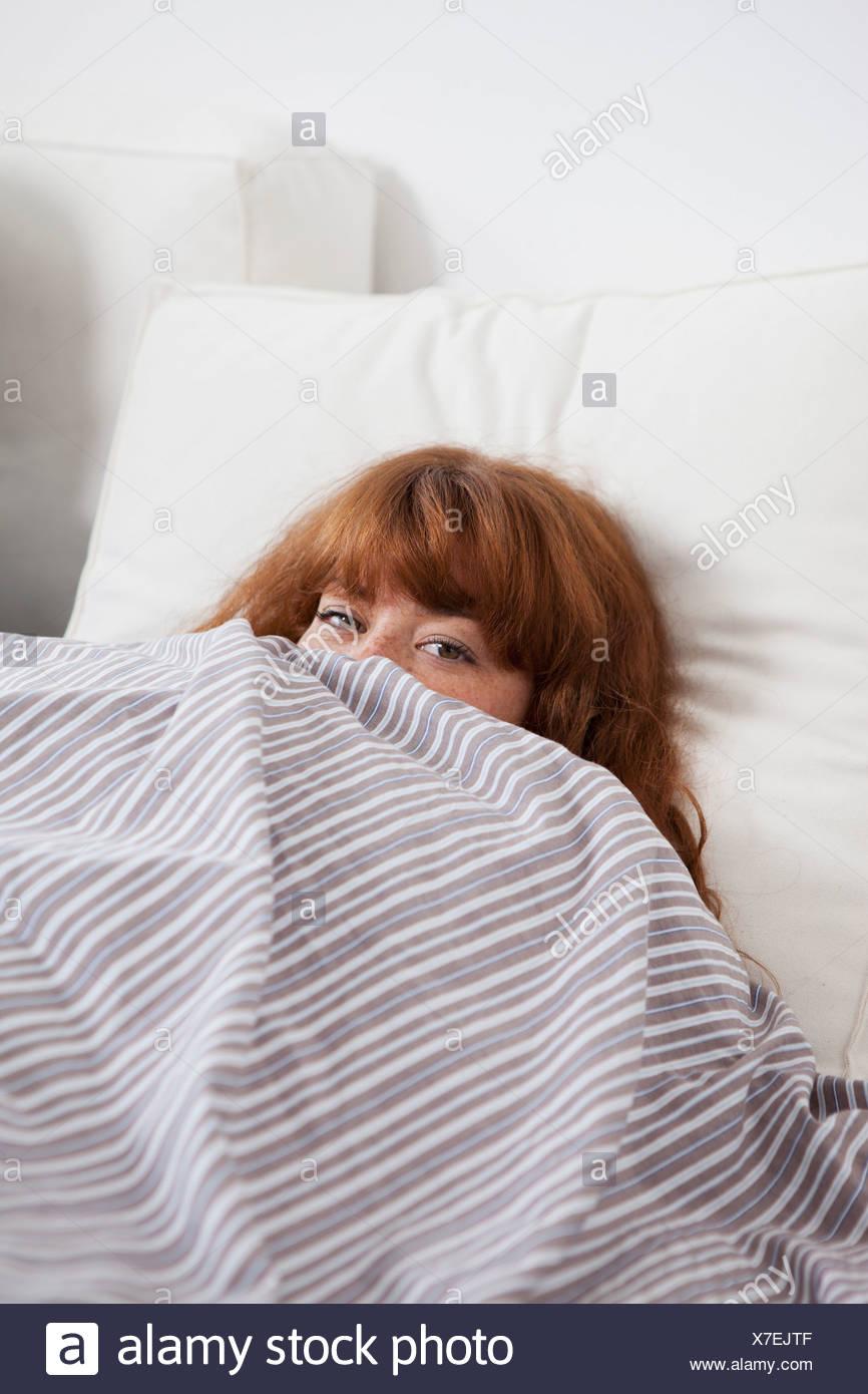 Una donna spiata da dietro un piumone nel letto Foto & Immagine ...