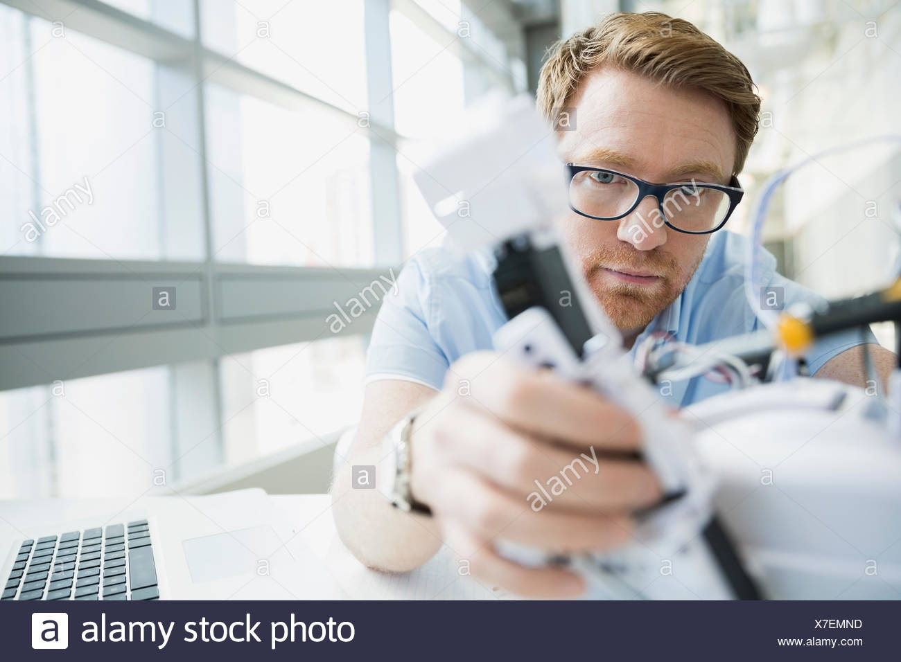 Ingegnere focalizzato esaminando robot Immagini Stock