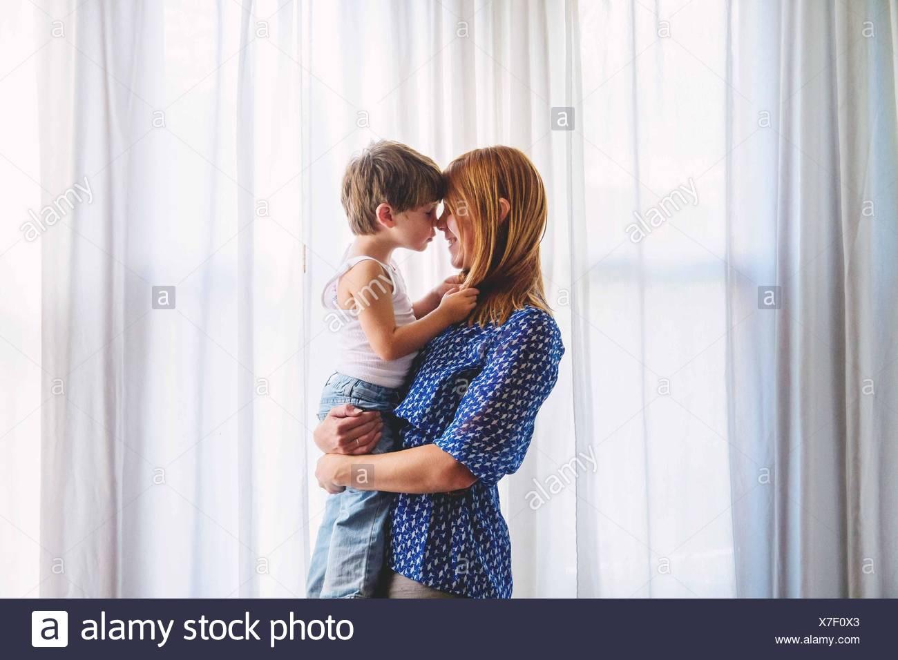 Mom azienda giovane ragazzo (2-3) e tocca naso Immagini Stock