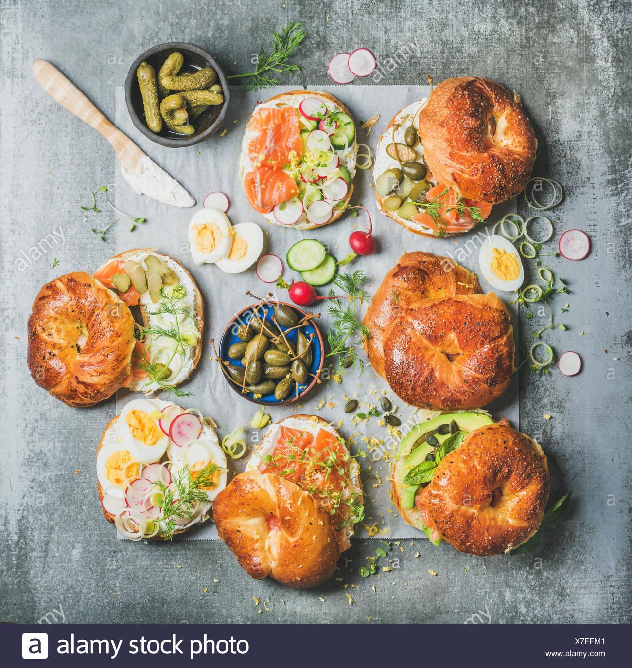 Varietà di bagel con salmone affumicato, uova, Rafano, avocado, cetriolo, verdi e crema di formaggio per colazione, pranzo sano o parte sul cemento grigio Immagini Stock