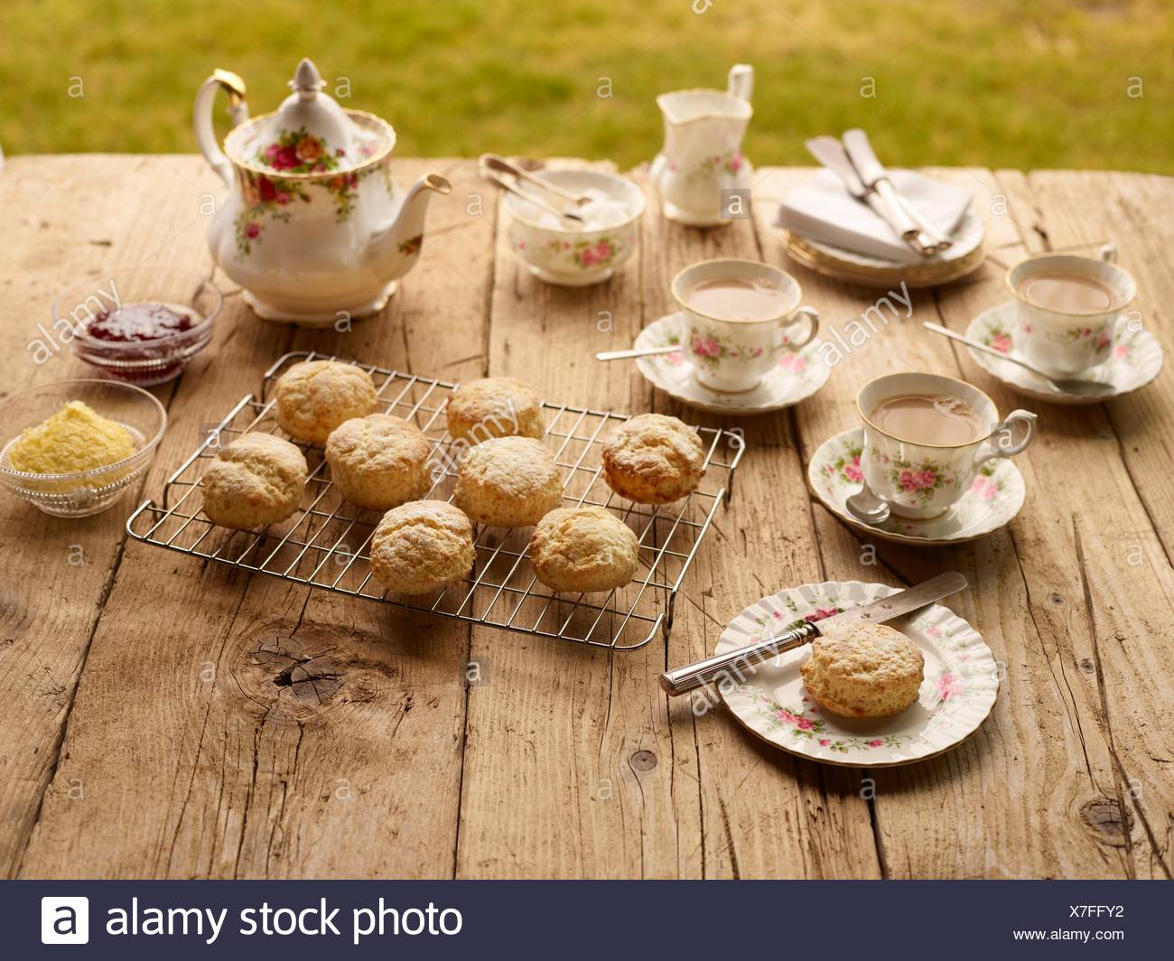 Tabella con il tè del pomeriggio con dolci appena usciti dal forno scones con marmellata e clotted cream Immagini Stock