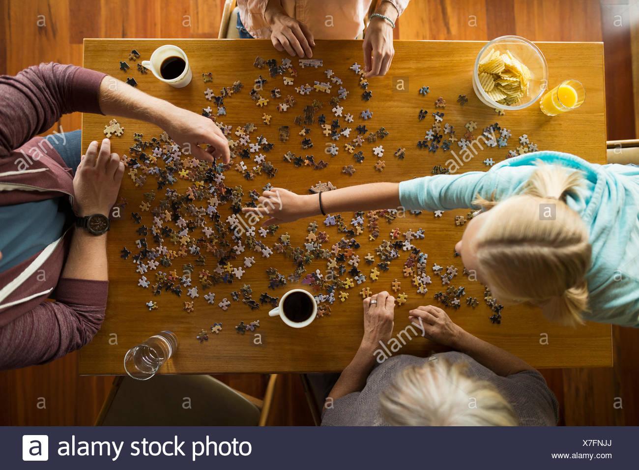 Vista aerea famiglia assemblaggio di puzzle a tavola Immagini Stock