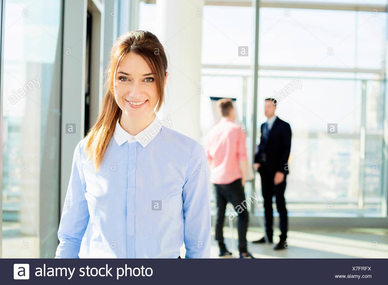 Ben vestito imprenditrice con colleghi in background Immagini Stock