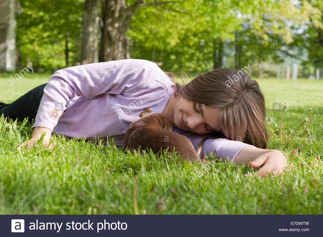 Adolescente cuddling cucciolo Immagini Stock