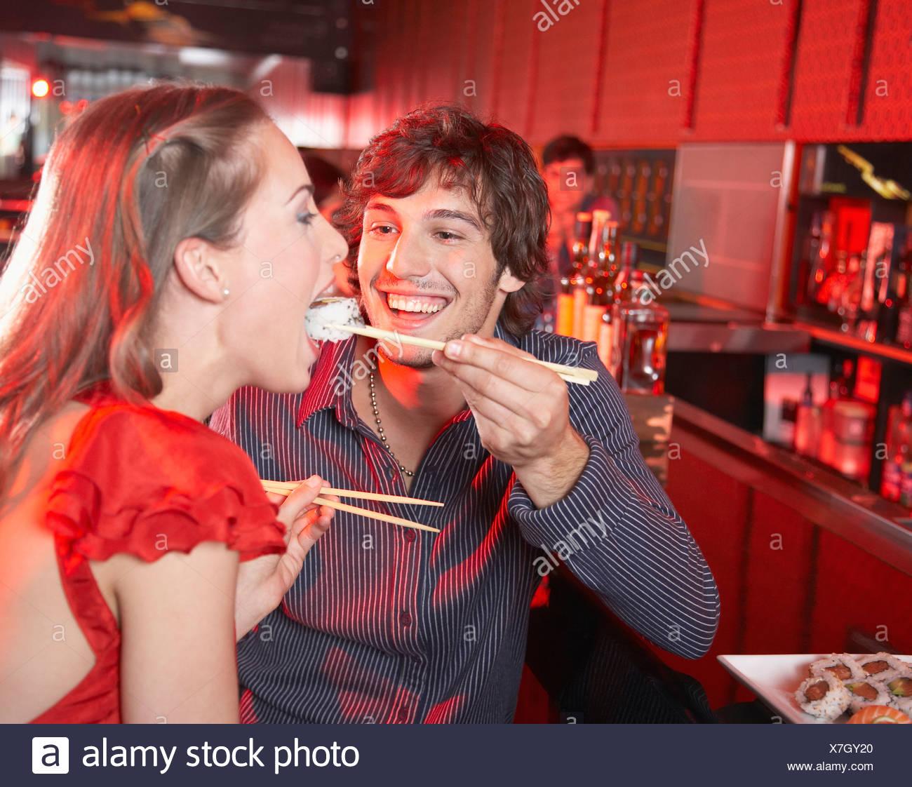 Uomo Donna alimentazione sushi in discoteca e sorridente Immagini Stock