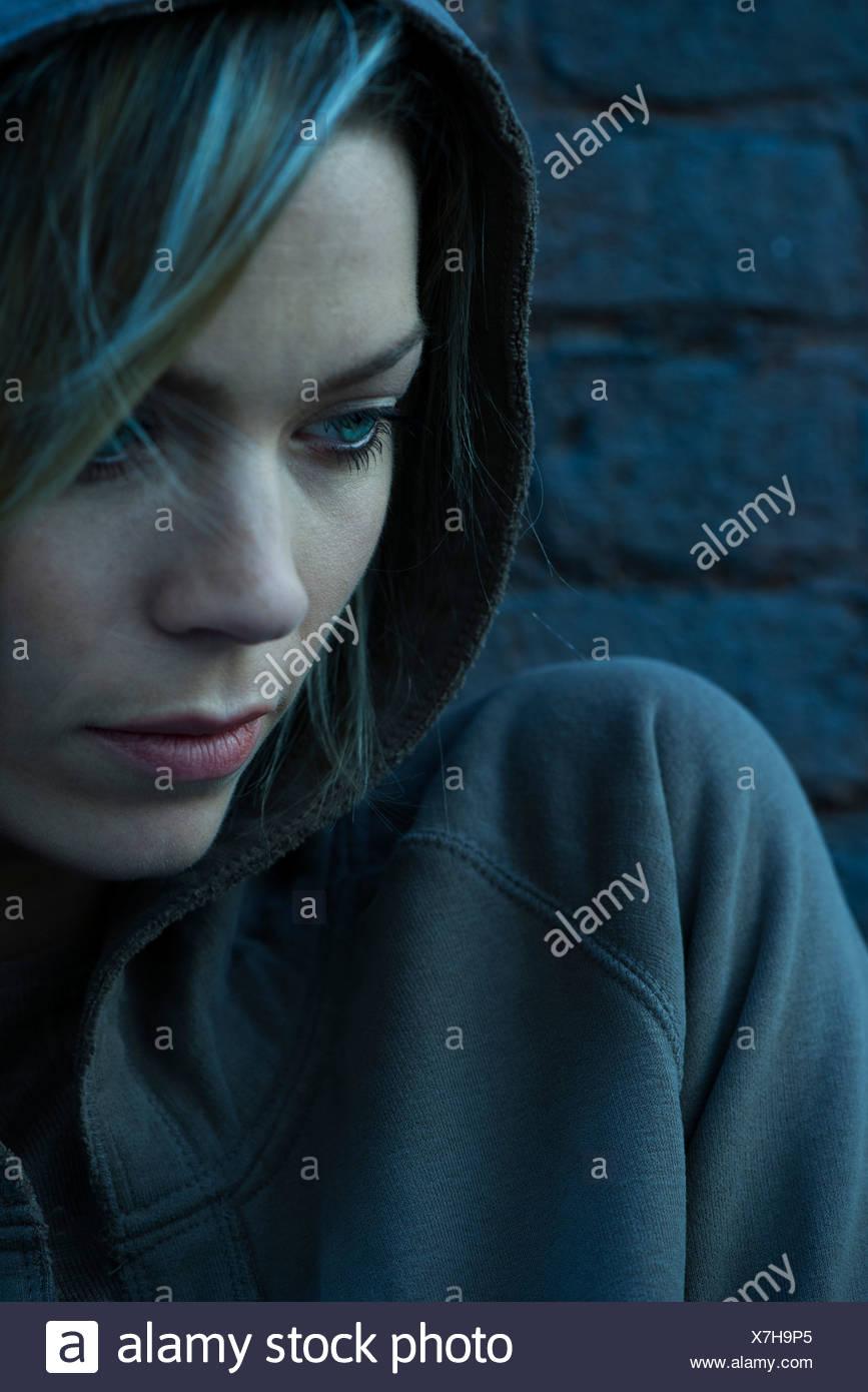 Donna in felpa con cappuccio pensively guardando lontano Immagini Stock