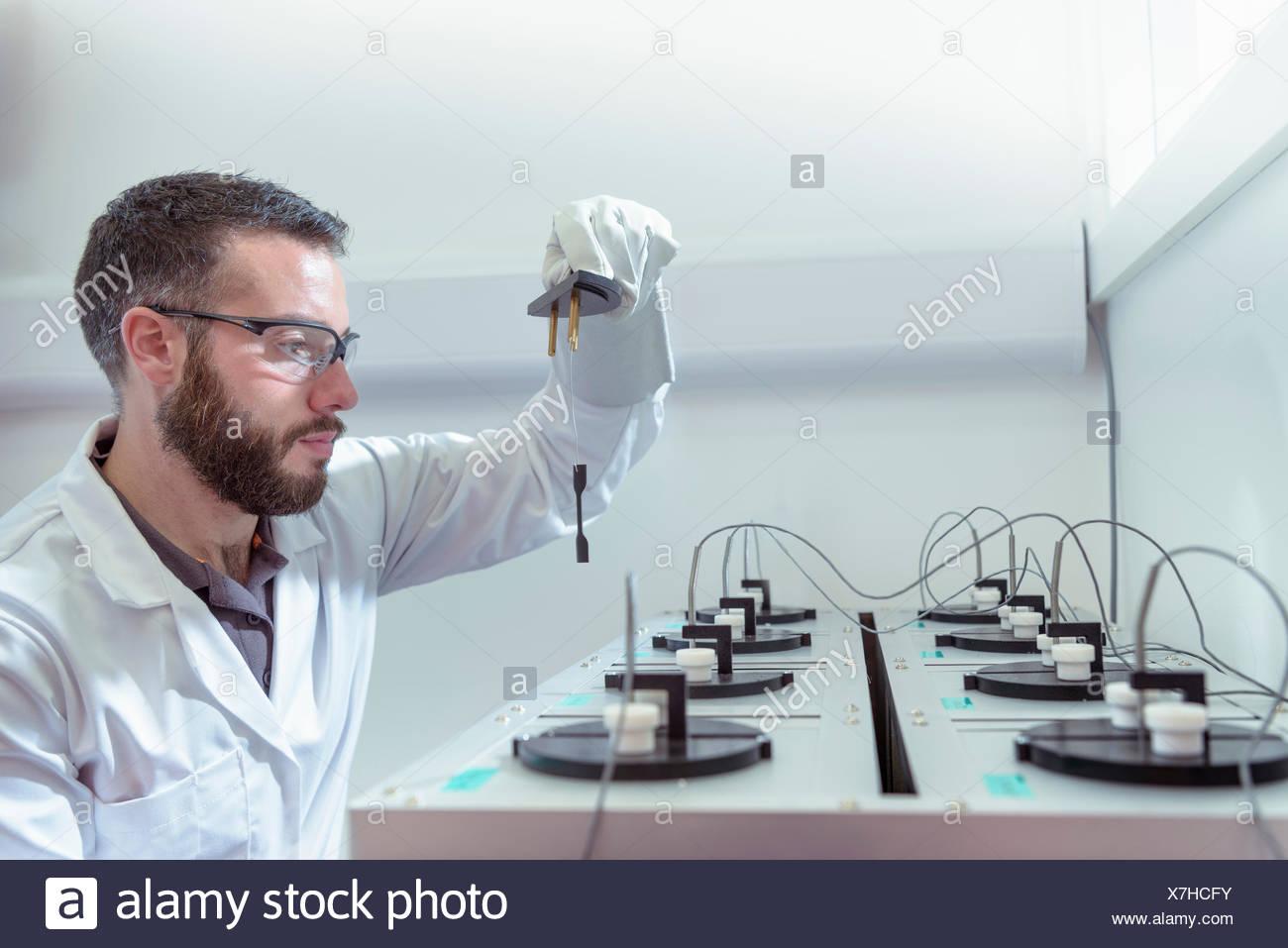 Scienziato età Prova cavo elettrico nel cavo elettrico laboratorio Immagini Stock