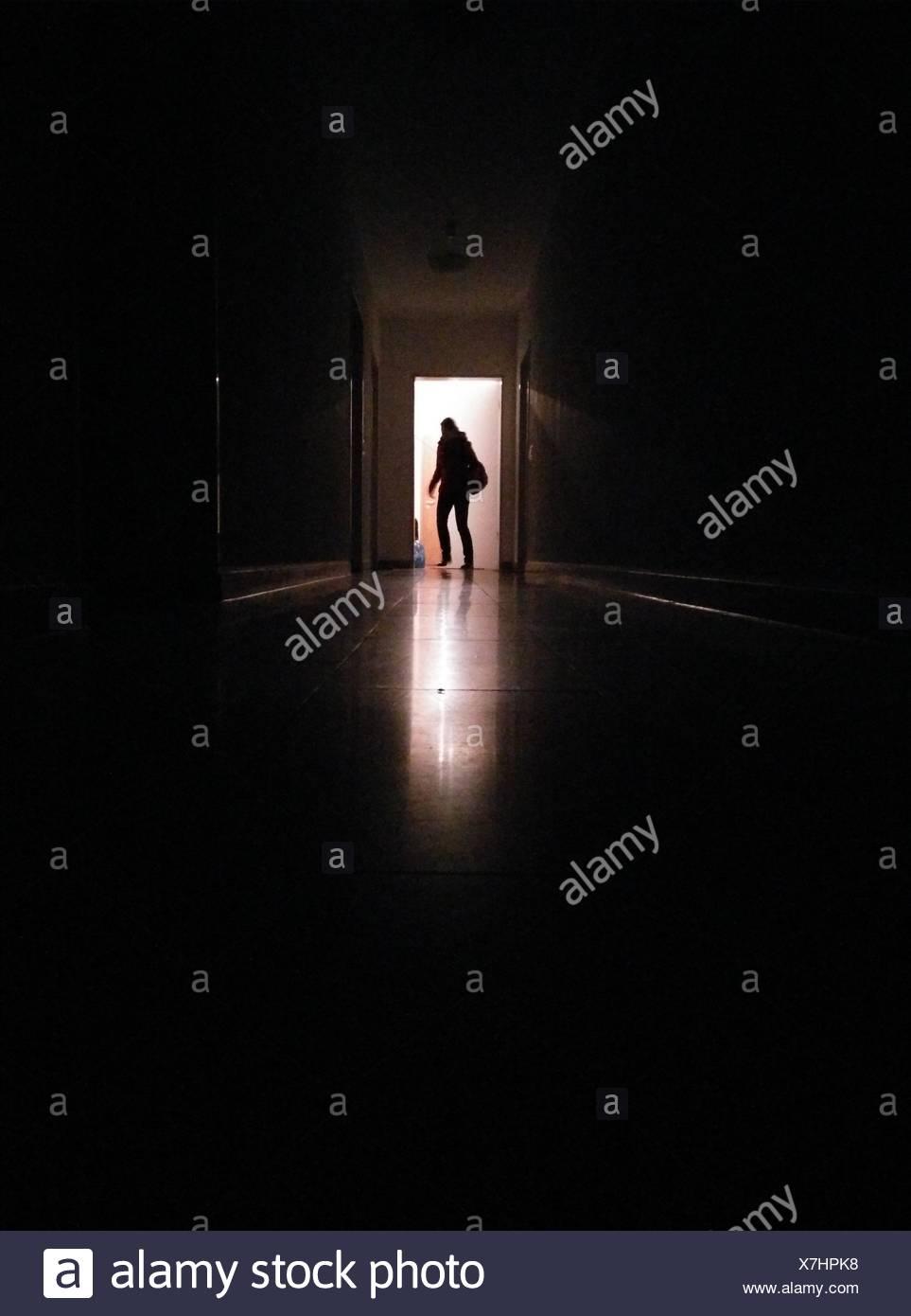 Silhouette persona nel corridoio entrando in camera illuminata Immagini Stock