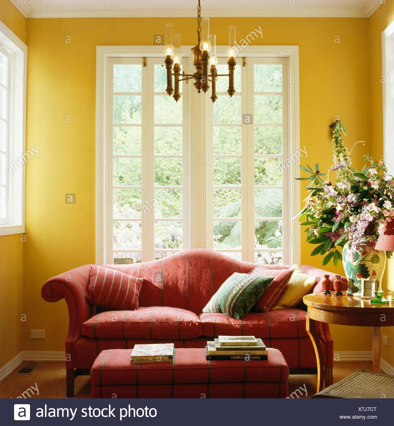 Divano rosso nella parte anteriore del francese windows in giallo ...