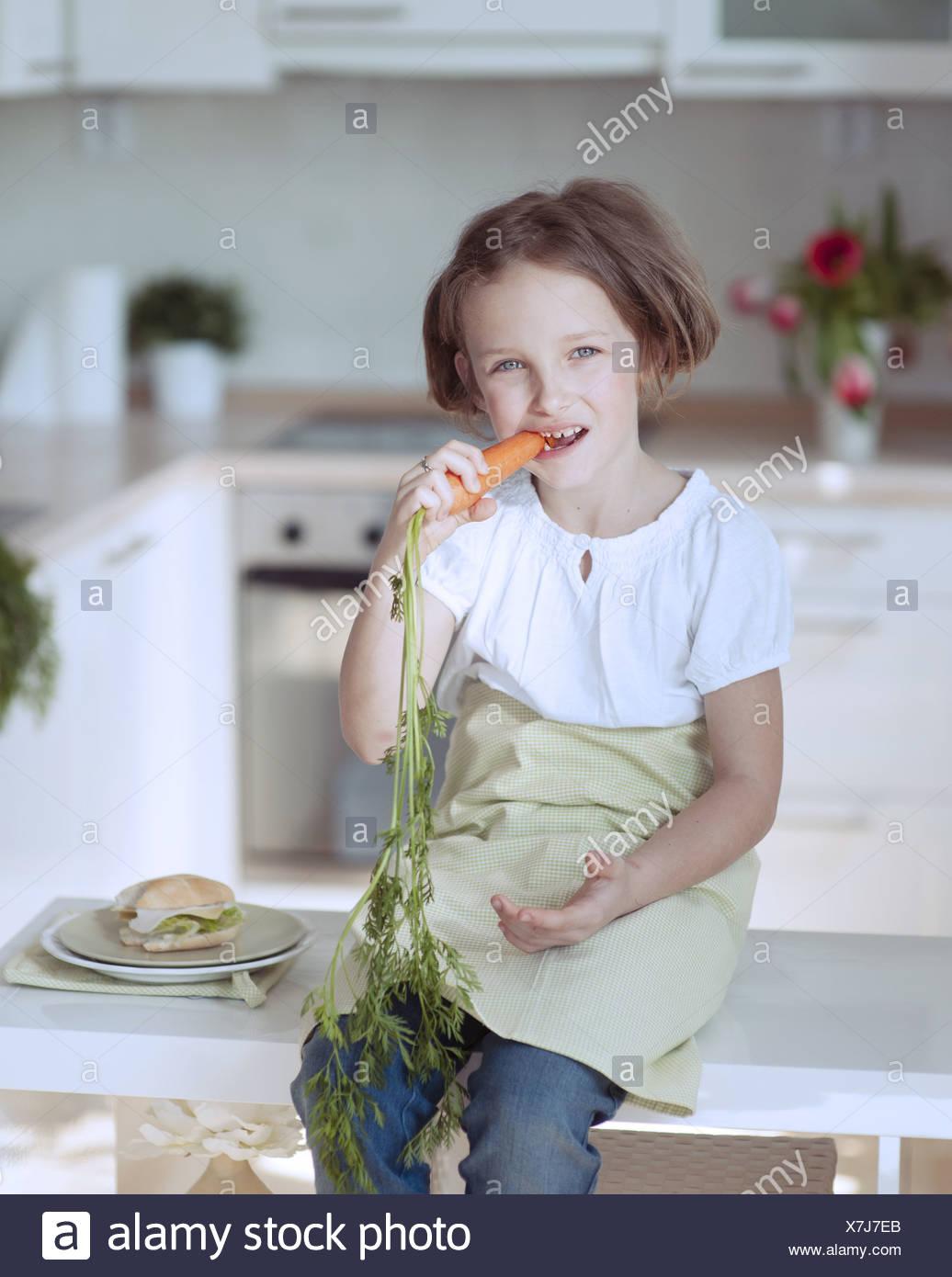 Ragazza giovane mangiando la carota Immagini Stock