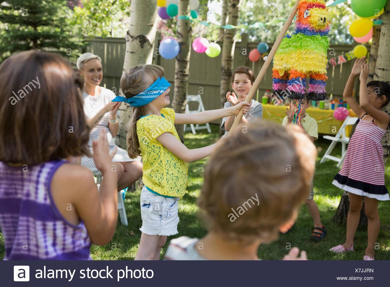 Bambini il tifo per gli occhi bendati ragazza a oscillante pinata Immagini Stock