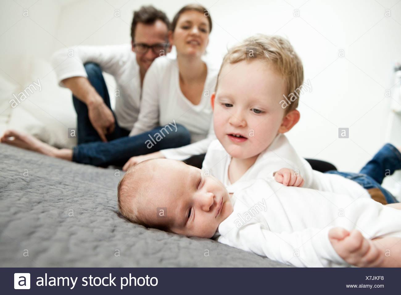 Ragazzo esaminando neonato fratello sul letto Immagini Stock