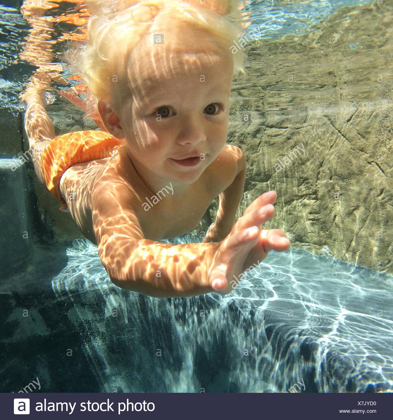 Ragazzo di nuoto sott'acqua in piscina Immagini Stock