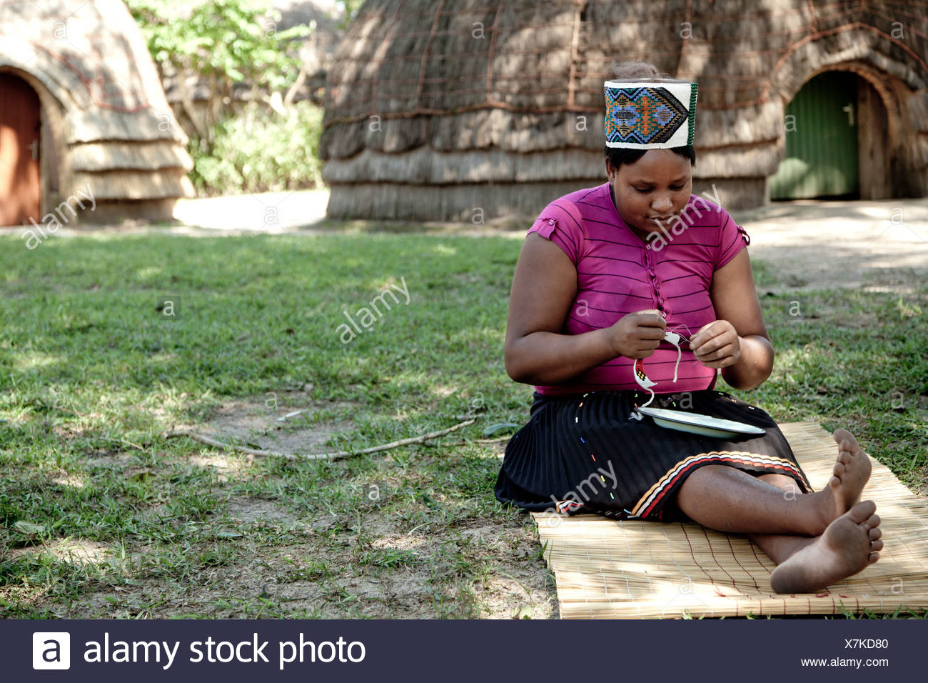 Donna africana vestito in abiti tradizionali si siede sul pavimento creando beadwork Immagini Stock