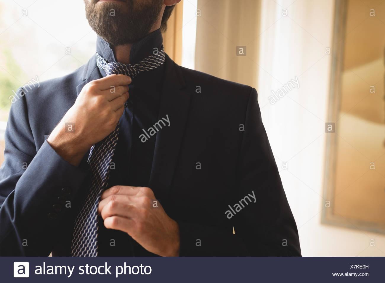 Uomo che indossa la cravatta a casa Foto Stock