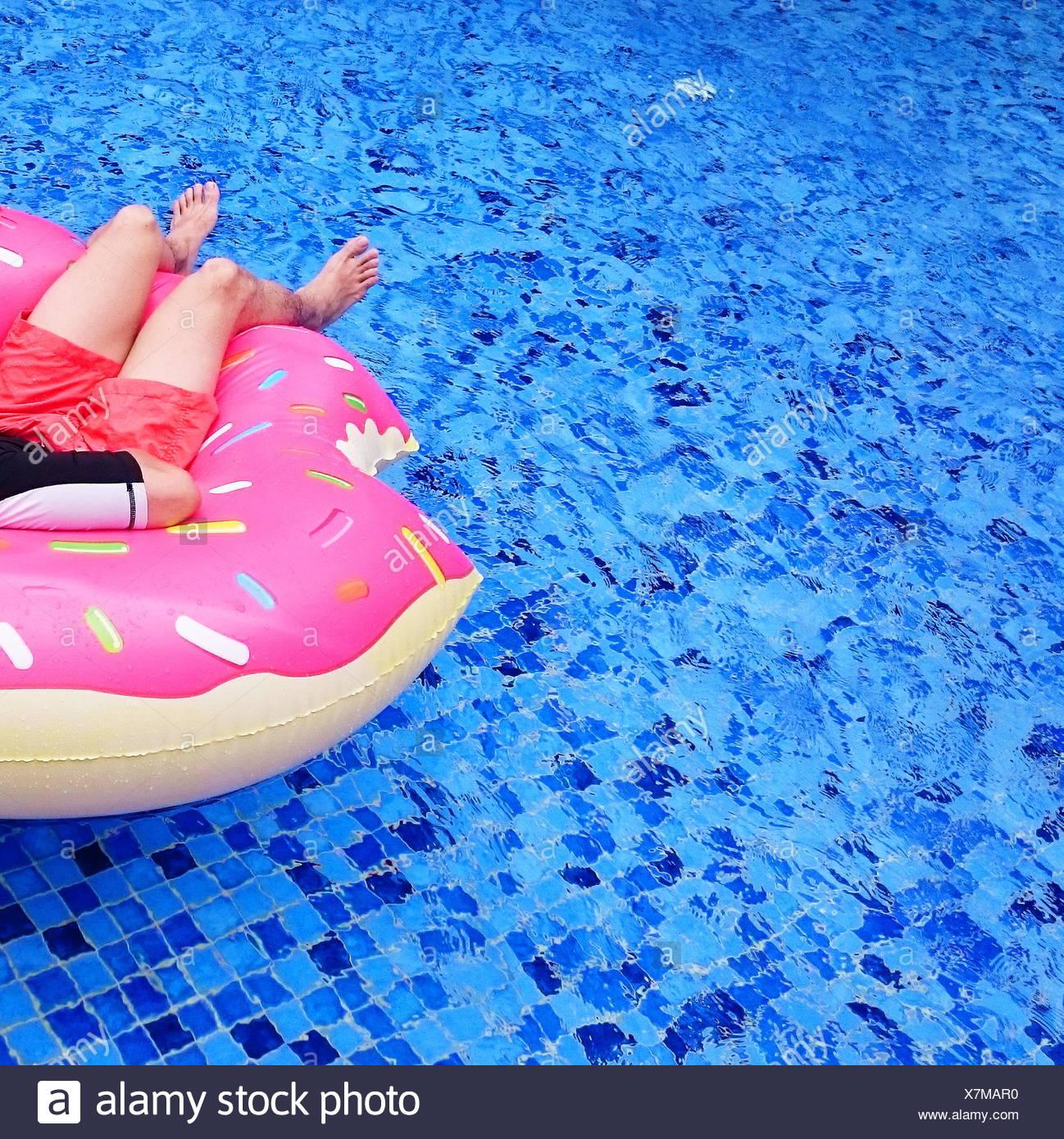 Uomo maturo rilassante sulla ciambella gonfiabile in una piscina Immagini Stock
