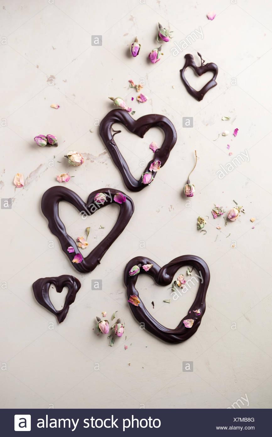 Cuori di cioccolato ed essiccato bocciolo di rosa sulla massa di luce Immagini Stock