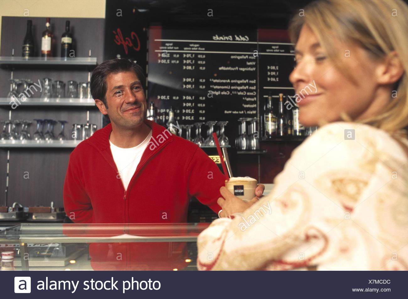 Donna, bar, contatore, Ordine cappuccino, lavoratore di ufficio, flirt, cafe, gelateria, all'interno, l'uomo, cameriere, flirt, sorriso, affetto, caduti, anticipi, fascino, ammiratore, mani, touch, scherzo, tease, scherzo, Latte Macchiato Foto Stock