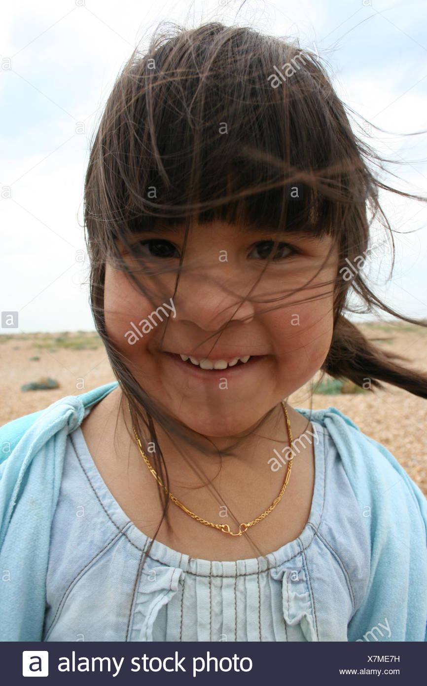 Ritratto di un sorridente ragazza con i capelli spazzate dal vento permanente sulla spiaggia Immagini Stock