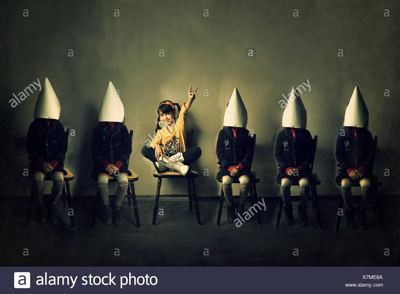 Ragazza in abbigliamento casual seduta su una sedia tra cinque ragazze che indossano uniformi Foto Stock
