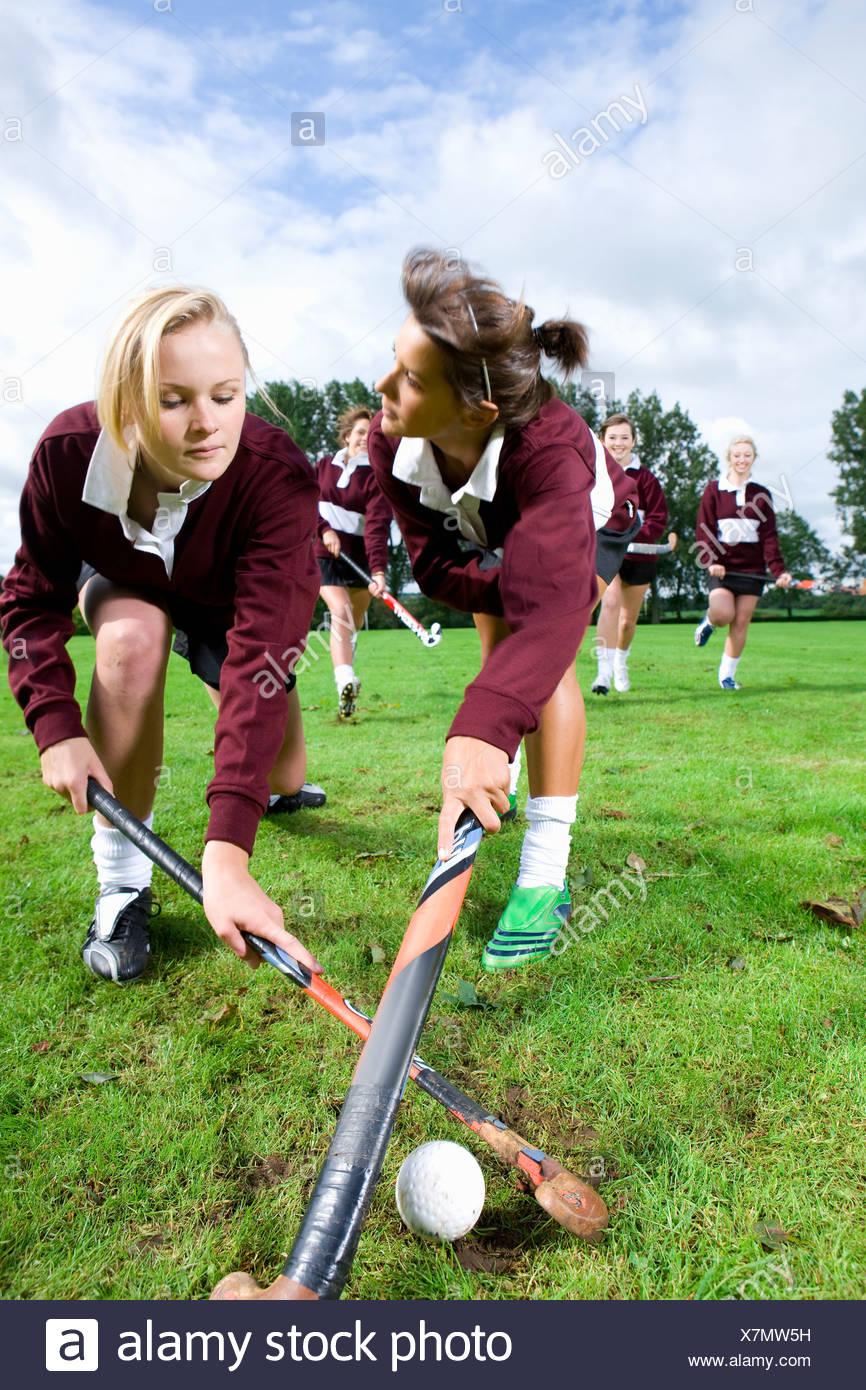 Le ragazze adolescenti la riproduzione di hockey su prato Immagini Stock