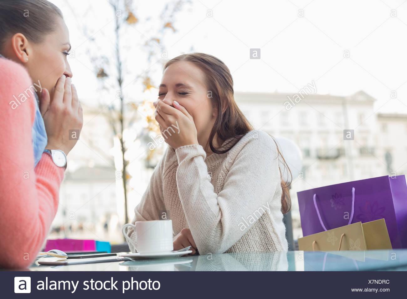 Felici donne che condividono i segreti a outdoor cafe Immagini Stock