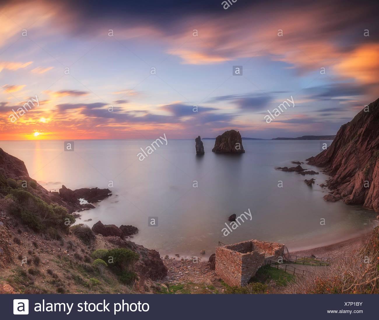 Portu banda spiaggia al tramonto, nebida, Iglesias, Sardegna, Italia. vi sono due grandi faraglioni (aragustieri) Immagini Stock