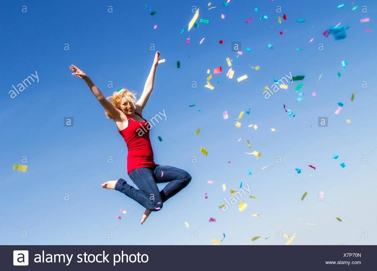 Giovane donna salta con coriandoli Immagini Stock